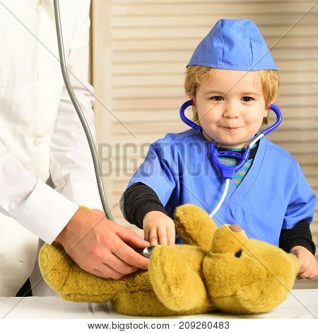 Health And Childhood Concept. Little Assistant Examines Teddy Bear.