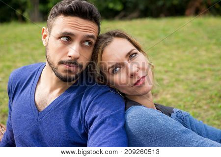 young couple sitting in park leaning against each other