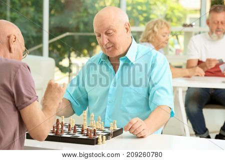 Elderly men playing chess at home