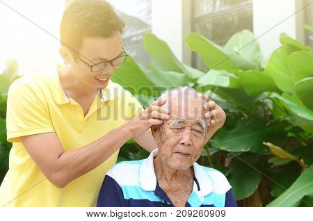 Asian old man headache son massaging father head. Chinese family senior retiree outdoors living lifestyle in the garden.