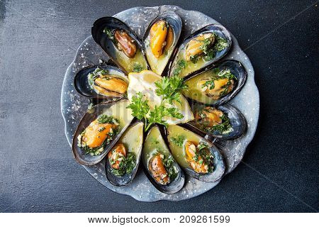 Mussels Baked With Butter And Parsley In Shell Mussels. Lemon, Parsley And Spices Around Plate On Da