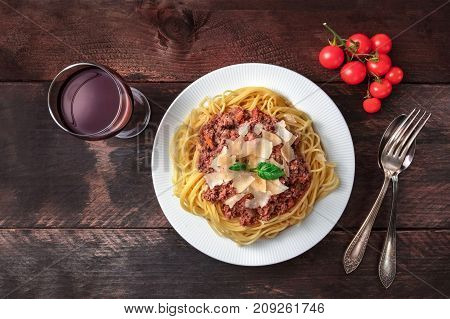 Overhead photo of plate pf bolognese pasta with grated parmesan cheese and fresh basil leaves, with fork and spoon, cherry tomatoes and glass of red wine, on dark rustic texture with copy space