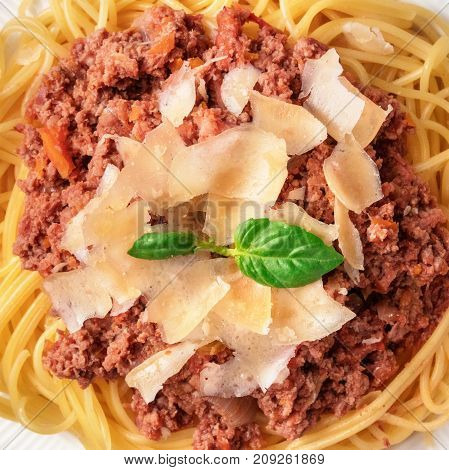 A square closeup photo of bolognese pasta with grated parmesan cheese and fresh basil leaves