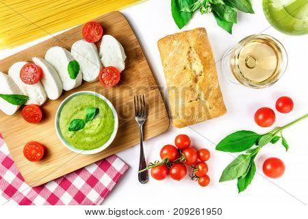 Overhead photo of an assortment of Italian foods on white background. Buffalo mozzarella cheese, cherry tomatoes, basil leaves, pesto sauce, spaghetti pasta, olive oil, ciabatta bread