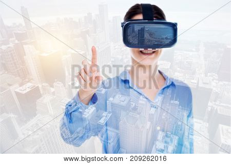 Exhilarating experience. Pleasant upbeat woman wearing a VR headset raising her index finger while her image being superimposed on the urban background