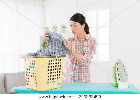 Woman Holding Grey Shirt Looking At Dirty Area