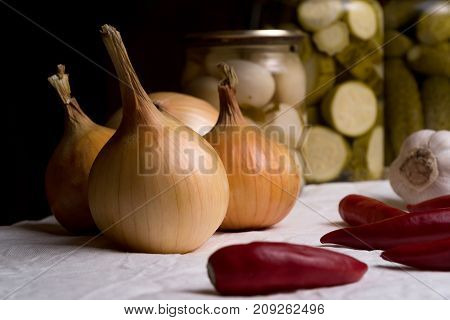 Onions Lie On A White Cloth Among Pepper, Garlic And Pickled Vegetables