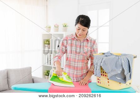 Young Pretty Mother Using Iron On Ironing Board