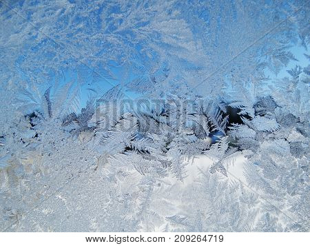 snowflakes ice pattern with sunlight on winter window glass