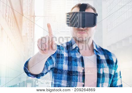 Ready to tap. Pleasant bristled man in a checkered shirt using a VR headset and raising his index finger as if ready to tap on a big screen