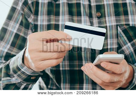 young man holding credit card and use smartphone for pay or shopping online concept.