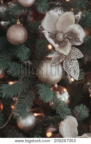 Group of silver and gold Christmas toys weigh on green branches Christmas tree closeup