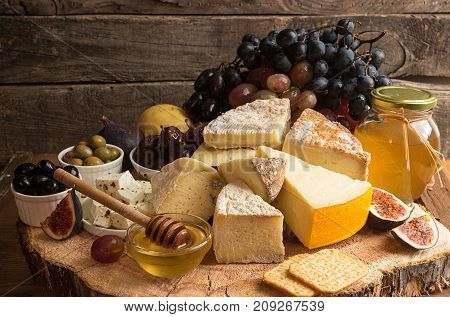 Food Composition With Blocks Of Moldy Cheese, Pickled Plums, Honey, Grape Bunch, Olives, Figs, Pear,