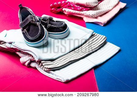 Folded Blue And Pink Bodysuit With Boat Shoes On It On Minimalistic Pink And Blue Background. Diaper