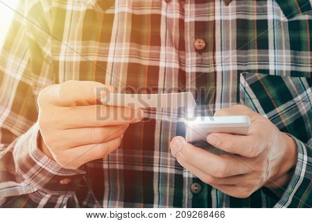 young man holding credit card and use smartphone pay shopping online concept.