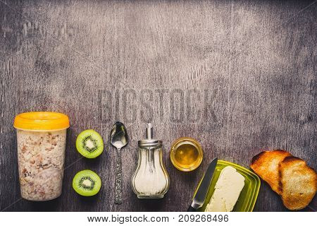 Healthy breakfast ingredients. Bowl of oat granola, fresh fruit and honey. Top view, copy space. Toned. Flat lay. Still life.