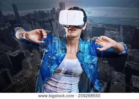 Exciting action. Beautiful young woman wearing a VR headset and playing an action game as if opening prison bars