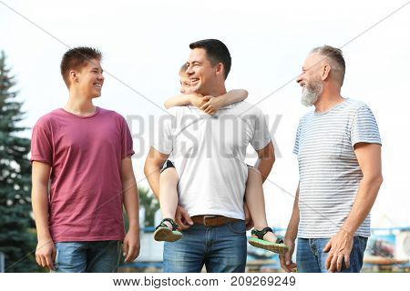 Cute boy with brother, daddy and grandfather outdoors
