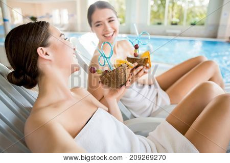 Laughing girls with tropical cocktails enjoying rest at luxurious spa resort