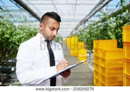 Young agro-engineer making notes on background of all year round vegetation