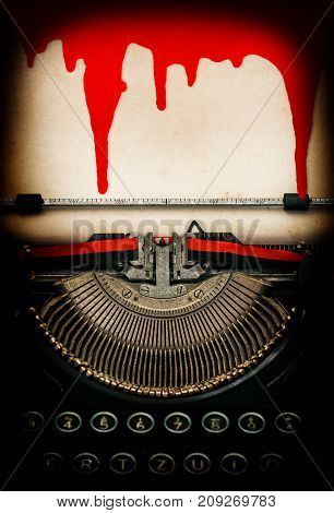 Antique typewriter and used textured paper sheet with blood. Halloween concept. Dark toned pictire