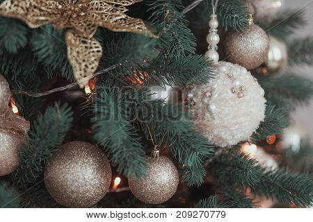 Gold Flower Christmas tree Decoration, white knitted ball hanging on fir with garland.