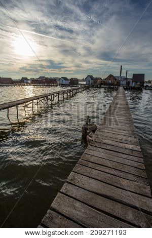 Sunset lake Bokod with pier and fishing wooden cottages, power plant in background, Hungary