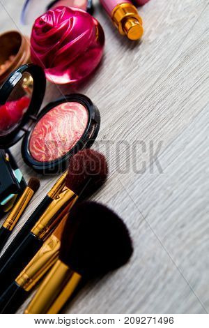 Set Of Decorative Cosmetics And Brushes On Grey Wooden Background. Various Makeup Products. Top View
