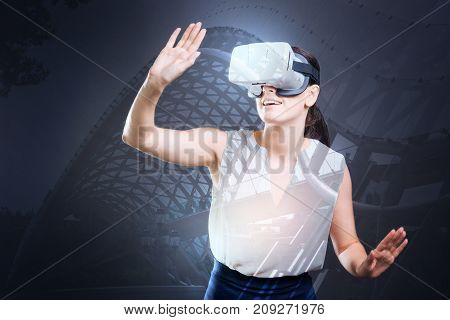 Totally immersed. Beautiful young woman playing a VR game, looking up and raising her hand ready to protect herself, being totally immersed into playing