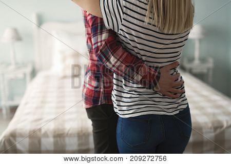 Portrait of romantic attractive couple hugging in bedroom