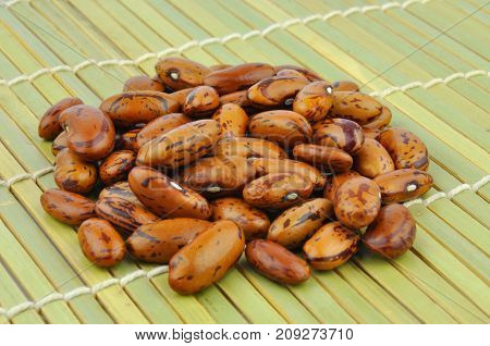Brown pinto beans on bamboo mat background
