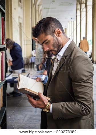 Side view of handsome man in elegant suit reading book in library.