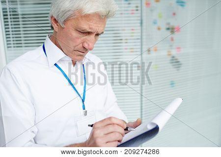 Senior investigator making notes about crime circumstances