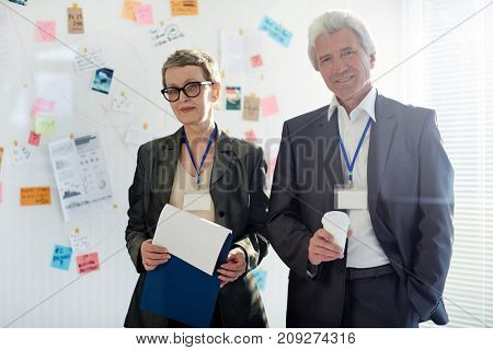 Two mature detectives in formalwear on background of whiteboard with crime evidence