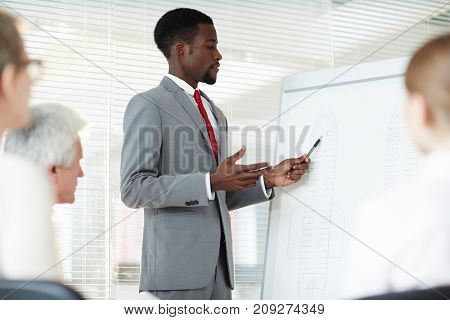 Young investigator explaining data on whiteboard to co-workers during crime survey