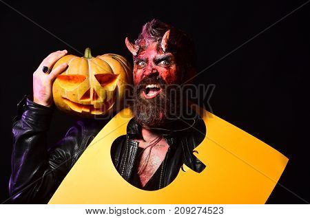 Demon With Horns And Mad Face Holds Jack O Lantern.