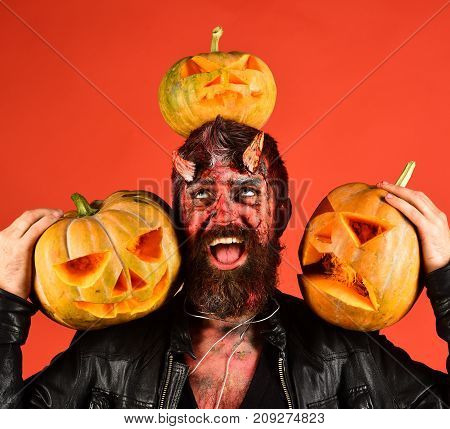 Halloween Party Concept. Man Wearing Scary Makeup Holds Pumpkins