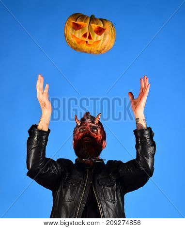 Man Wearing Scary Makeup Throws Pumpkin Up On Blue Background.