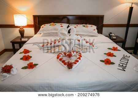 Bed decorated with flowers and towels in hotel room