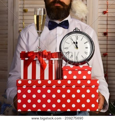Man With Beard Holds Boxes, Champagne Glass And Alarm Clock