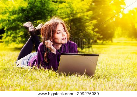Young Woman Using Laptop In The Park Lying On The Green Grass