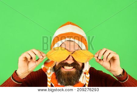 Hipster With Beard And Smile Closes Eyes With Leaf