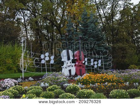 autumn in a public park decorative musical instruments with notes and a tiny key in a flower bed