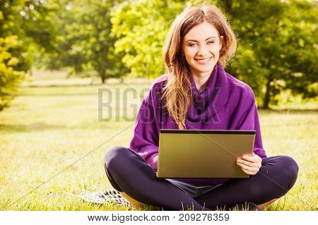 Young Woman Using Laptop In The Park Sitting On The Green Grass