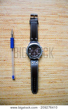 Wristwatch with writing pen for fulfilling the goals