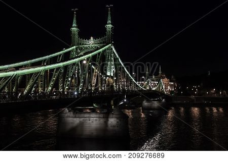 Illuminated Iron Bridge Over Danube River In The Night