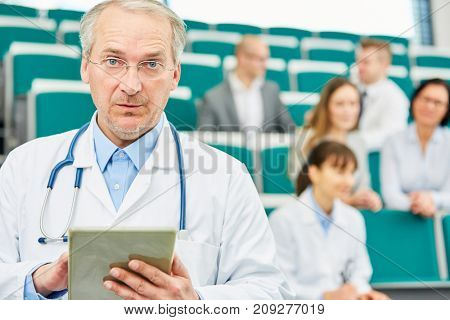 Senior as competent medicine professor holding tablet with authority