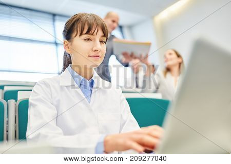 Young woman as medicine student with laptop learn in apprenticeship