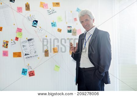 Elegant detective in suit standing by whiteboard with evidence of crimes