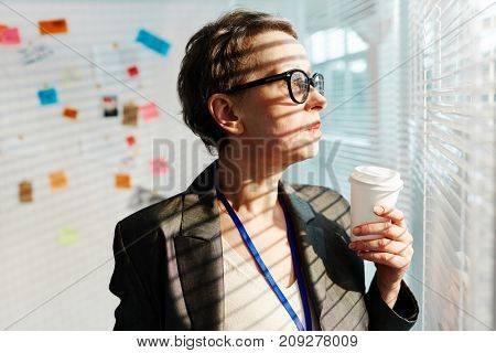 Mature officer with glass of coffee looking through venetian blinds on window